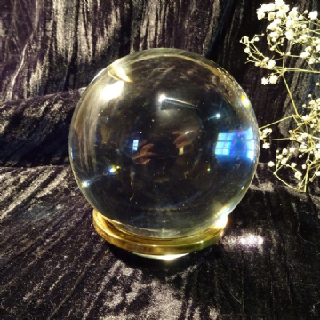 Crystal Ball Sitting on a Glass and Brass Dish